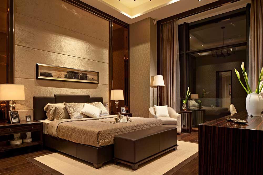 卧室背景墙以金色丝绒装饰与床头等宽的装饰画,皮质床尾凳方便衣物的放置,美观实用。